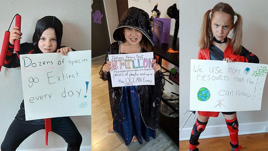 Three kids in costumes hold signs with environmental messages on them.