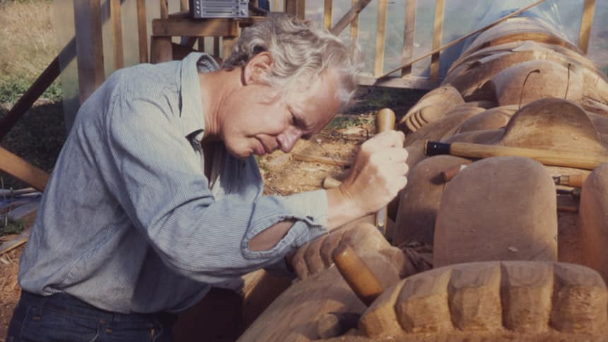 A photo of artist Bill Reid carving.
