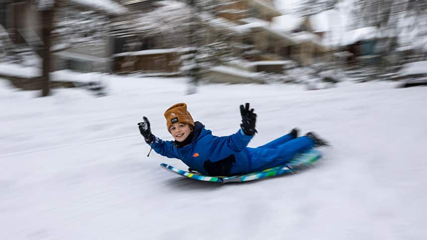 Boy sleds down residential street.