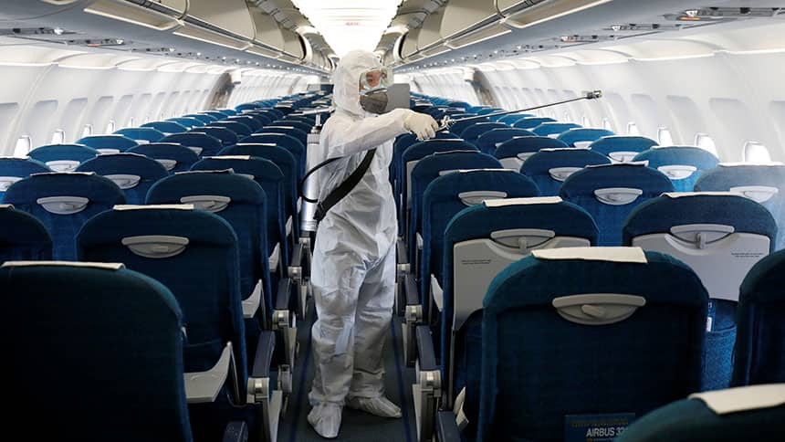 A person in a hazmat suit from head to toe sprays the inside of an airplane.