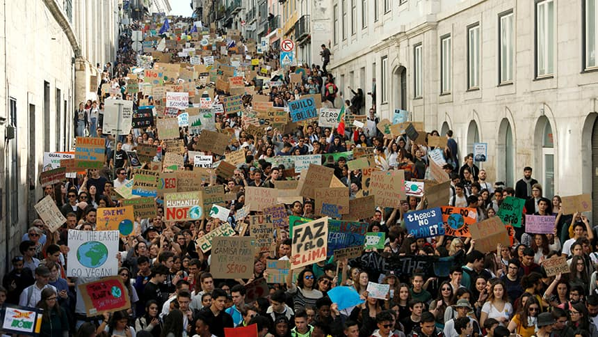 A crowd of people holding signs fills a street.