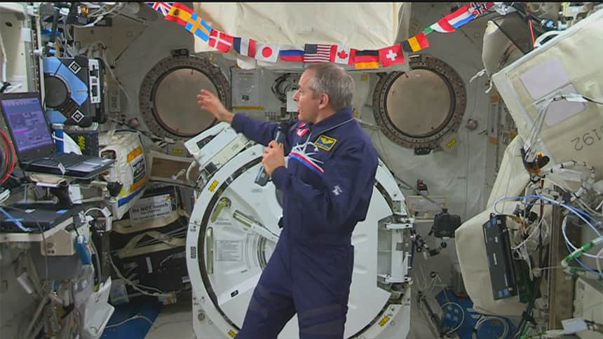 An astronaut points to a row of flags as he floats in space