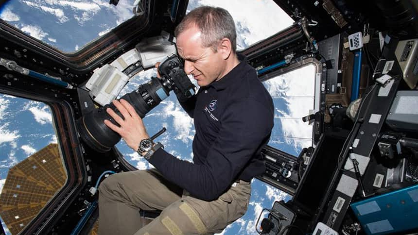 An astronaut takes pictures with the Earth through window beside him.