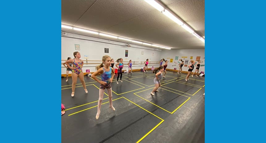 Young ballet dancers dancing in a studio. They are all within their own space, marked by yellow tape on the floor.