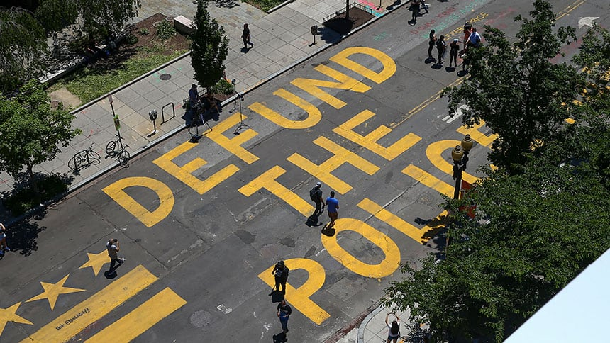Yellow paint on city street says Defund the police