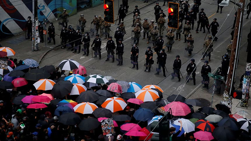 Protesters with umbrellas stand across from a line of police officers.