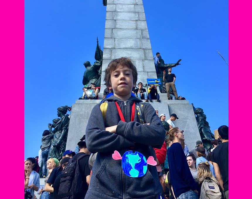 A boy at a climate rally in front of a statue.