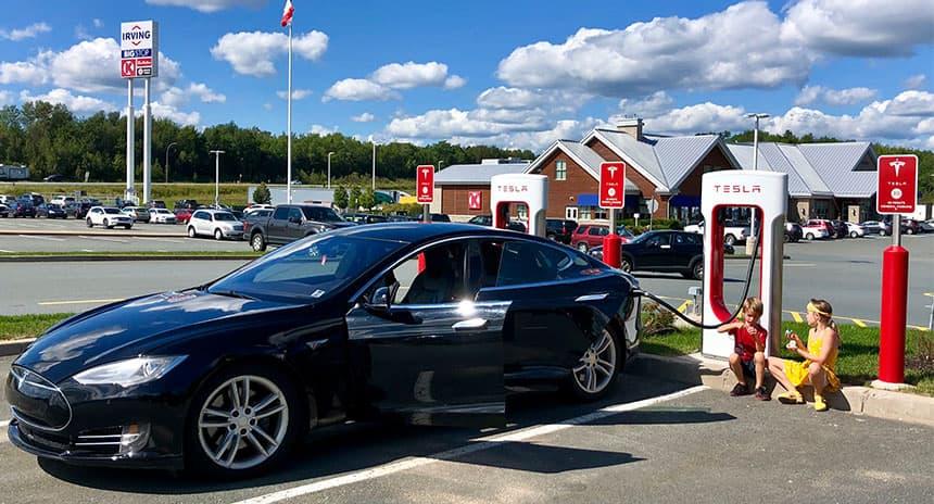 A car at a charging station at a gas station.