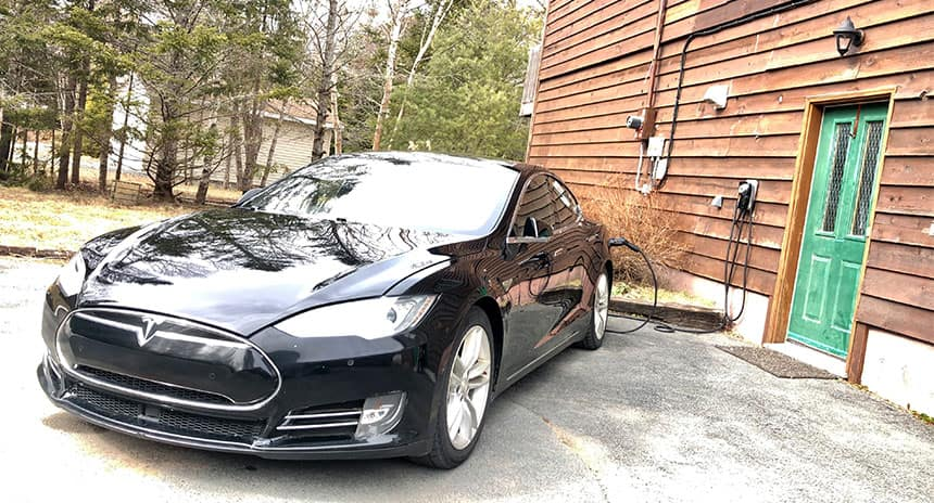 A Tesla plugged into a charging station in front of a house.