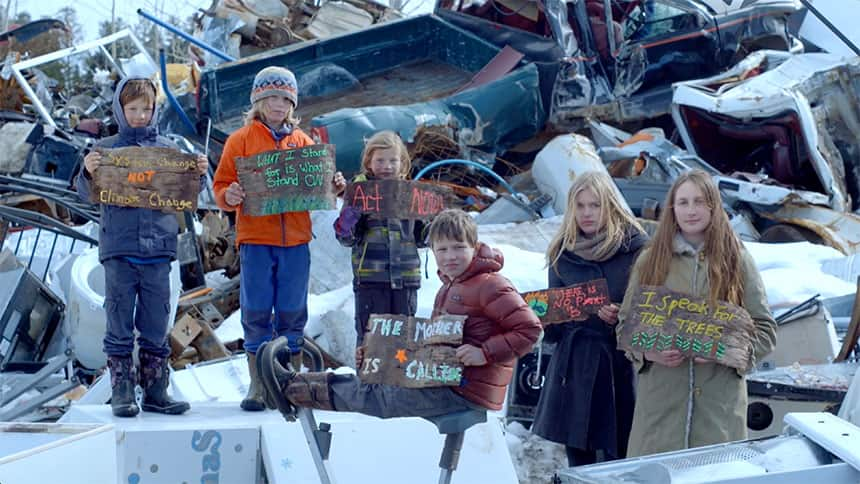 A group of kids hold signs about protecting the planet, standing in front of a garbage dump