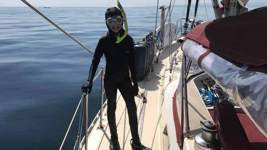 A girl stands on a boat in a wet suit with a snorkel.