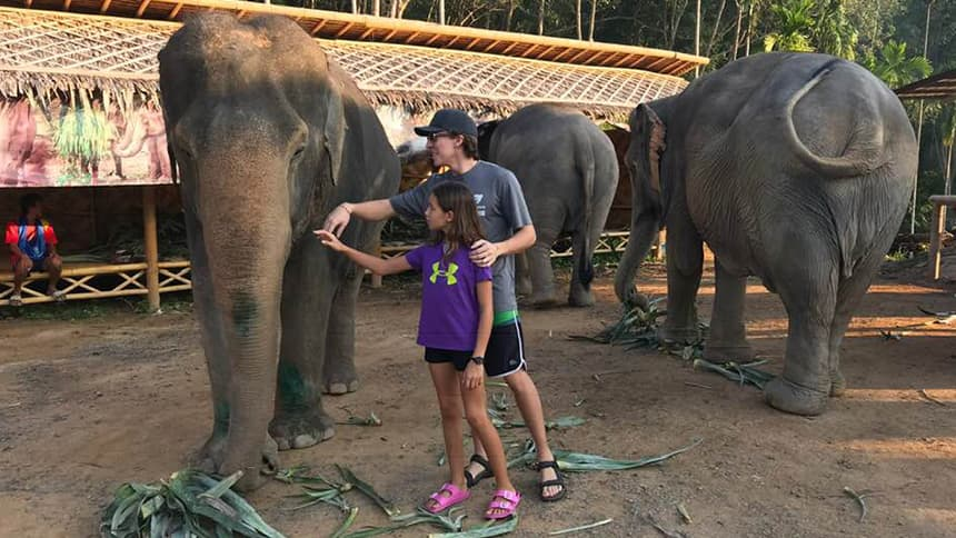 A girl and her older brother pet an elephant.
