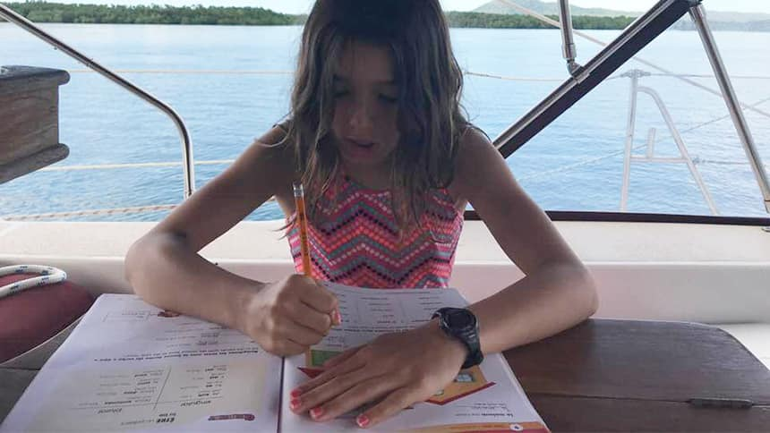A girl sits at a table on a boat doing school work,