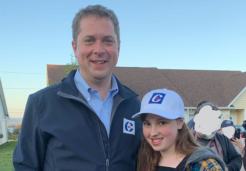Andrew Scheer stands next to Esther Uhlman. Both are wearing Conservative Party gear.