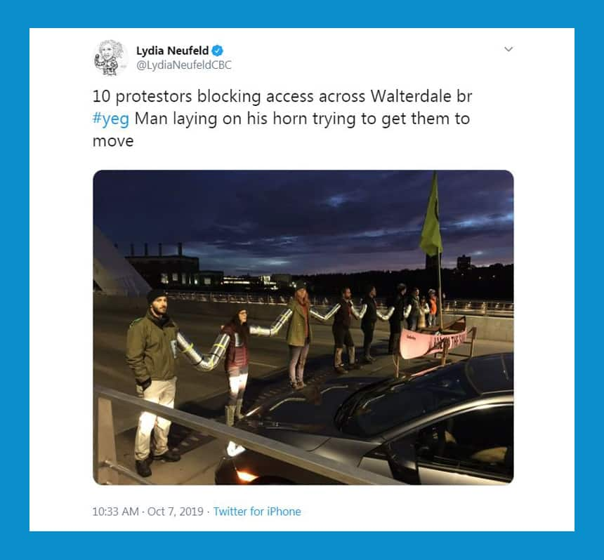 Tweet from Lydia Neufeld shows chain of people holding hands to block bridge access with text: 10 protesters blocking access across Walterdale bridge. Man laying on his horn trying to get them to move.