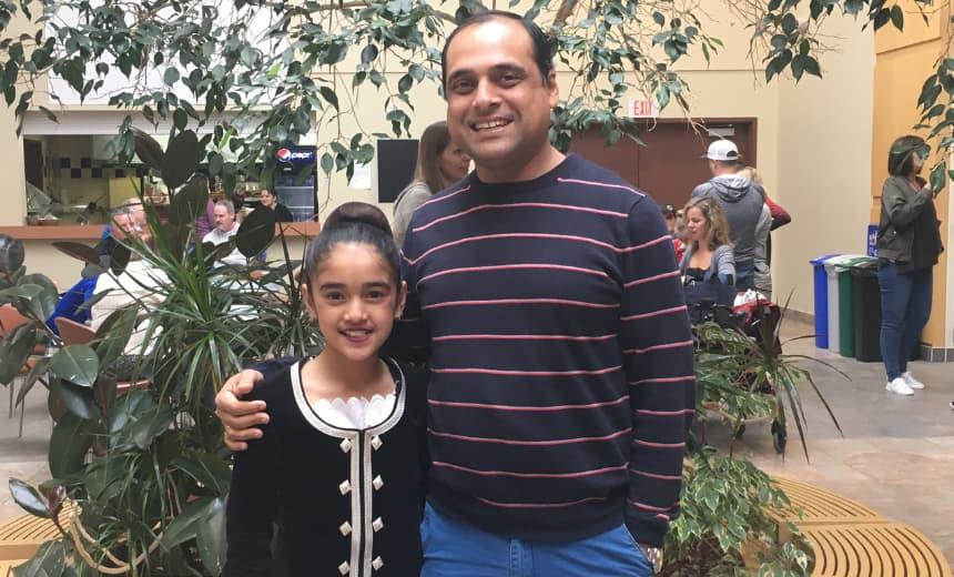 Yashita in her highland dancing uniform standing beside her dad.