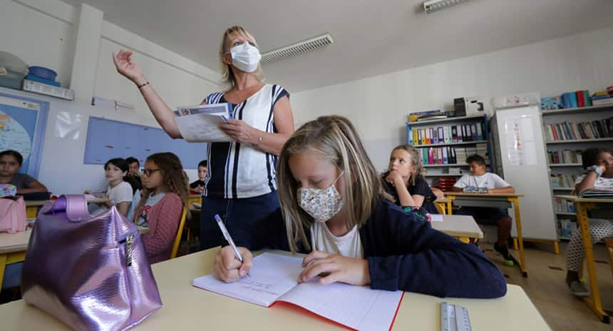 A teacher in class in class, teaching to students with a mask on.