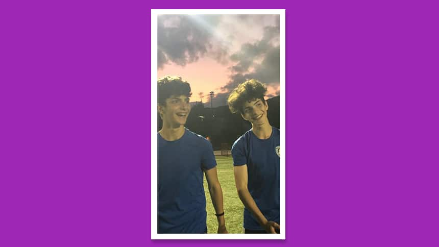 Twin boys smiling on a soccer pitch as the sun sets.
