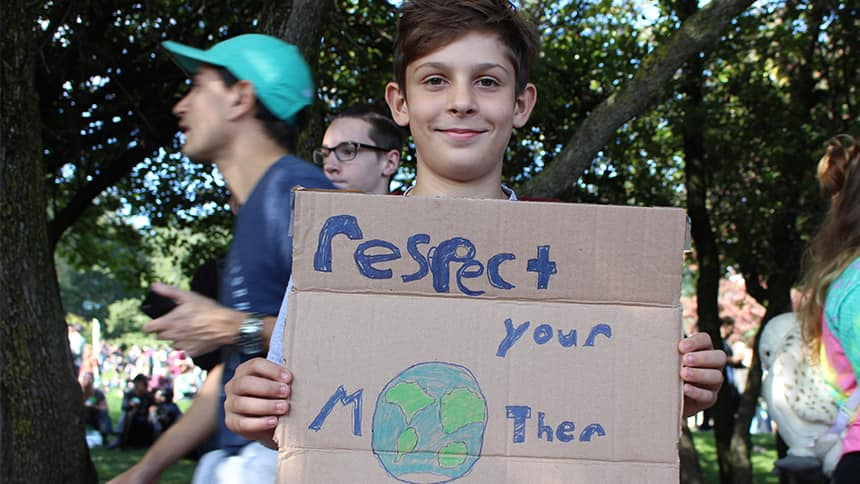 A kid with a sign that says Respect your Mother with a picture of the Earth