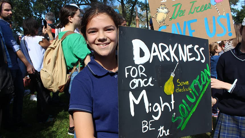 A girl with a sign that says