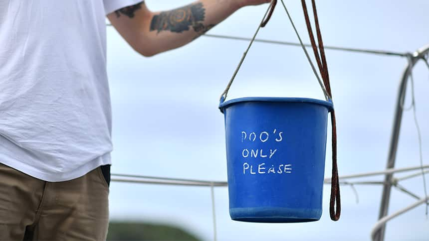 A man holds a bucket that says Poos only please