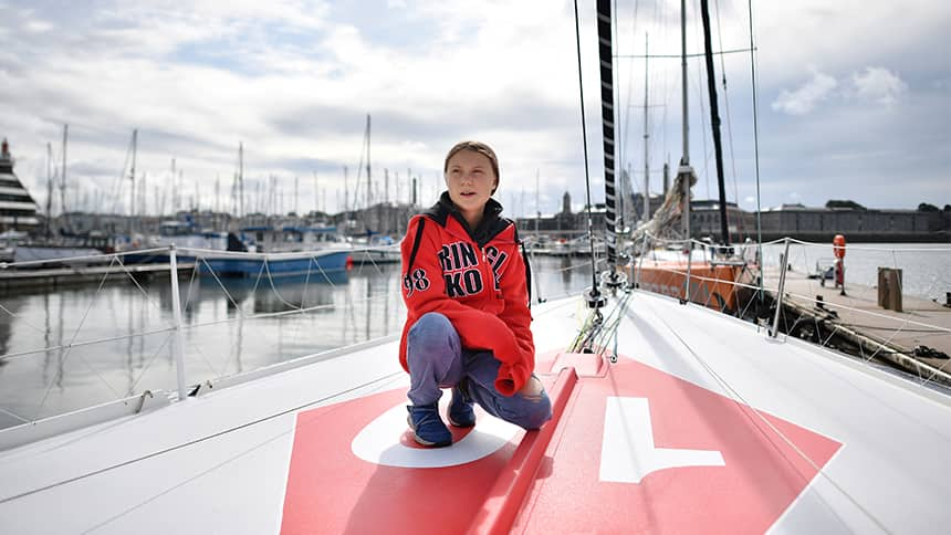 A teen crouches on the deck of a sailboat in a harbour.