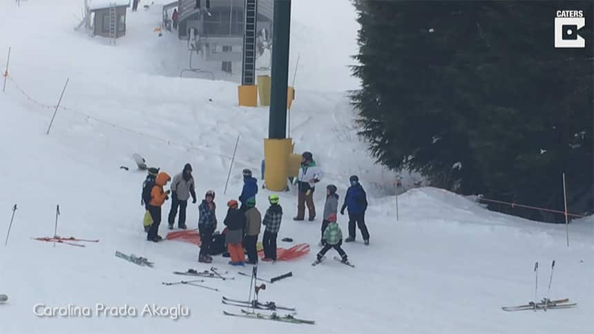 A crowd of 12 people sand in the snow, looking at a person lying on an orange net.