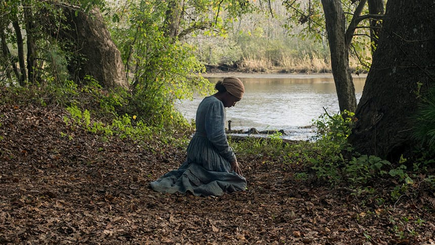 A woman sits looking down in the woods beside a river.