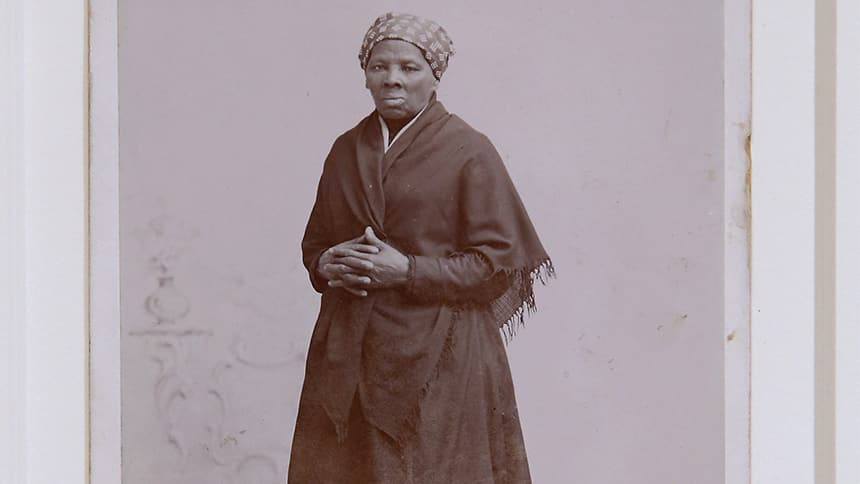An old black and white photo of a black woman in a long dress.