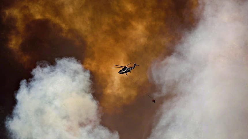 Helicopter flies through smoke and ash.