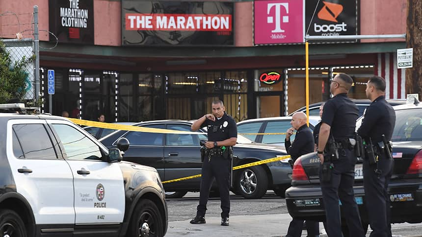 A police officer speaks into a walkie talkie in a parking lot with police tape around the front of a store.