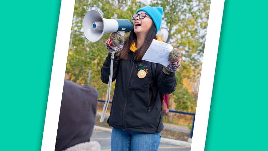 A teen yells into a megaphone.