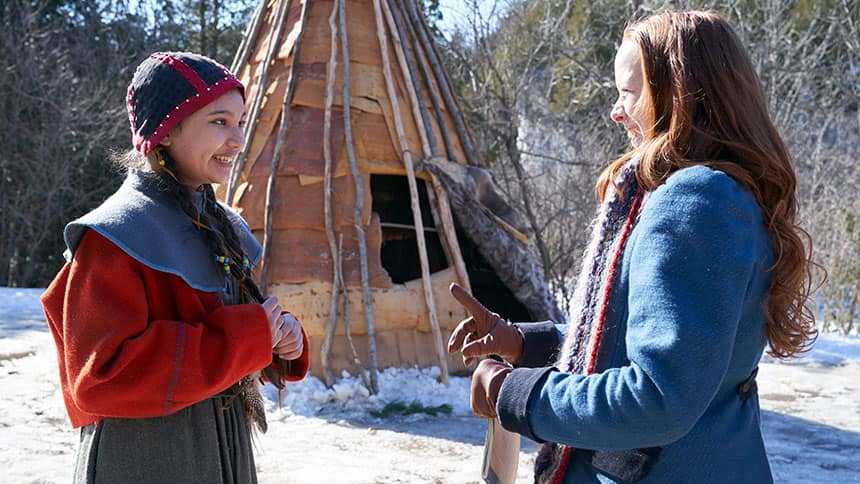 Kiawentiio Tarbell stands in costume next to Amybeth McNulty in front of a teepee.