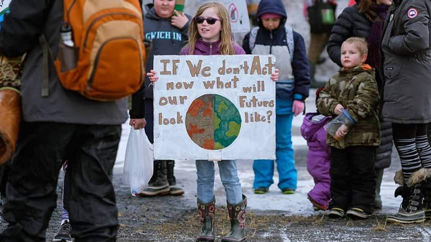 Girl holds sign that says If we don't act now what will our future look like? With picture of planet.