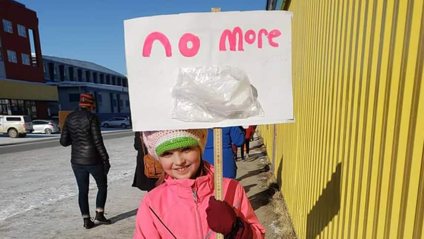 Girl holds sign that says No More above a plastic bag