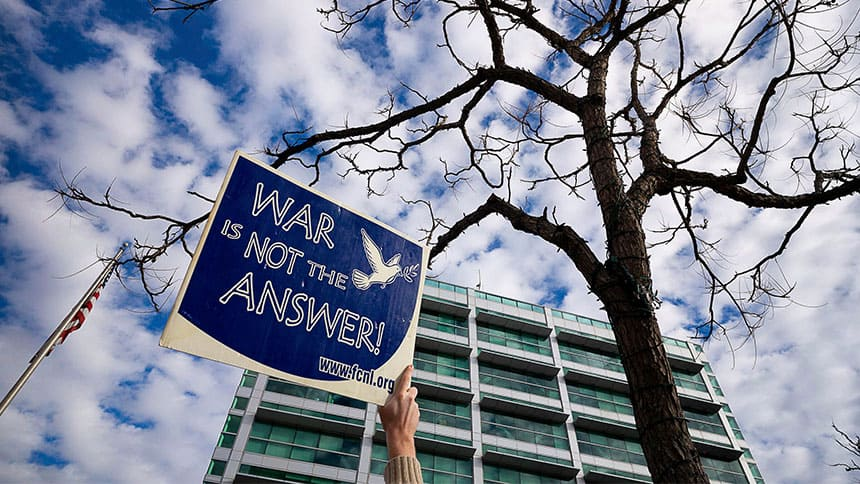 Protester holds sign up to the sky that reads: War is not the answer.