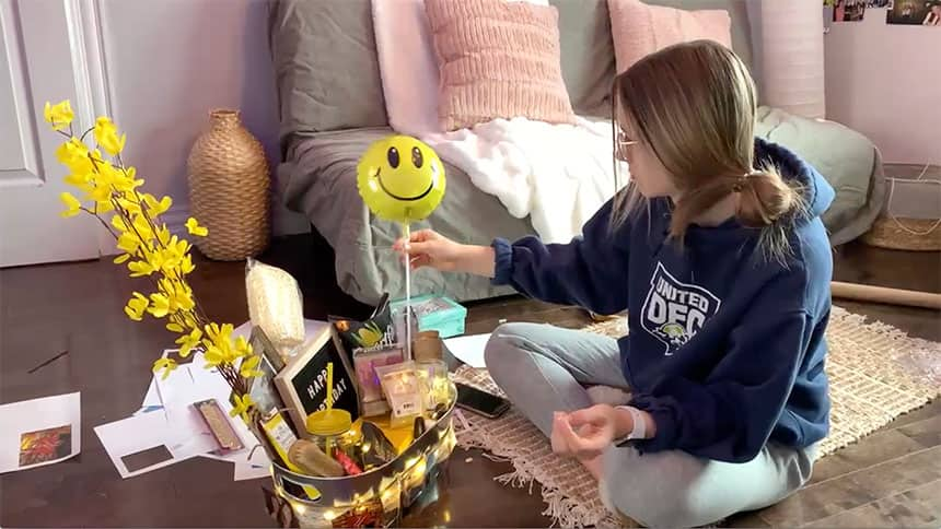 A teen puts together a colourful gift basket.