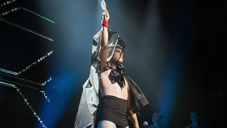 A performer stands on stage with an arm in the air.