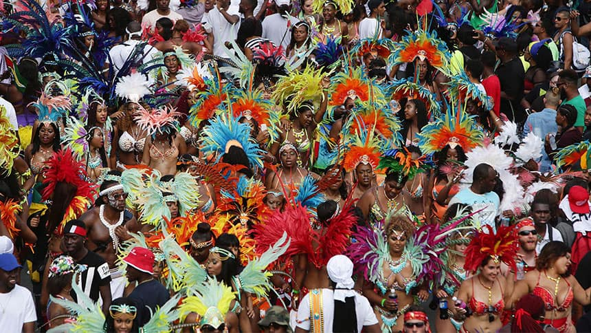 Crowd of people wearing elaborate parade outfits.