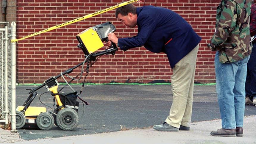 A man uses a ground-penetrating radar on a street.