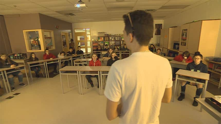 A student stands in front of a classroom speaking to students.