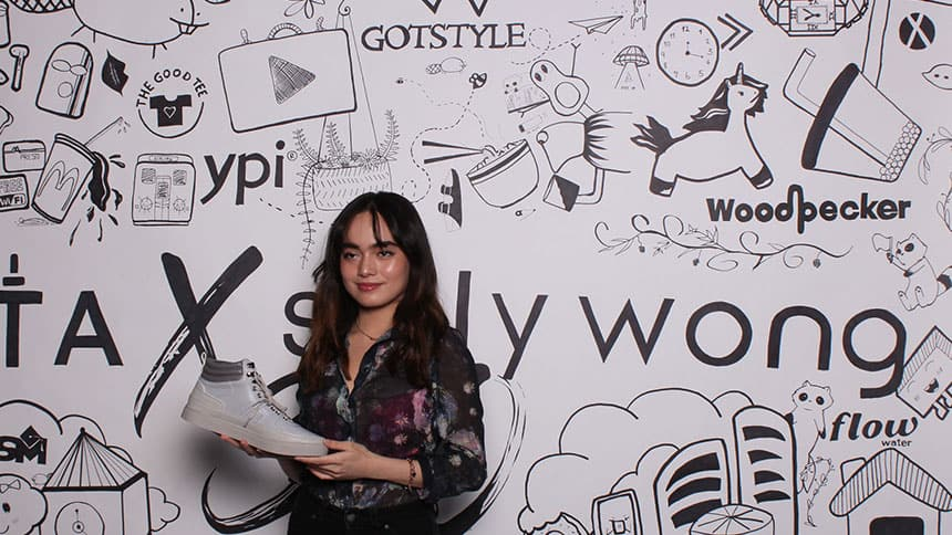Ylaijah Besa holds the shoe in front of a backdrop of her designs.