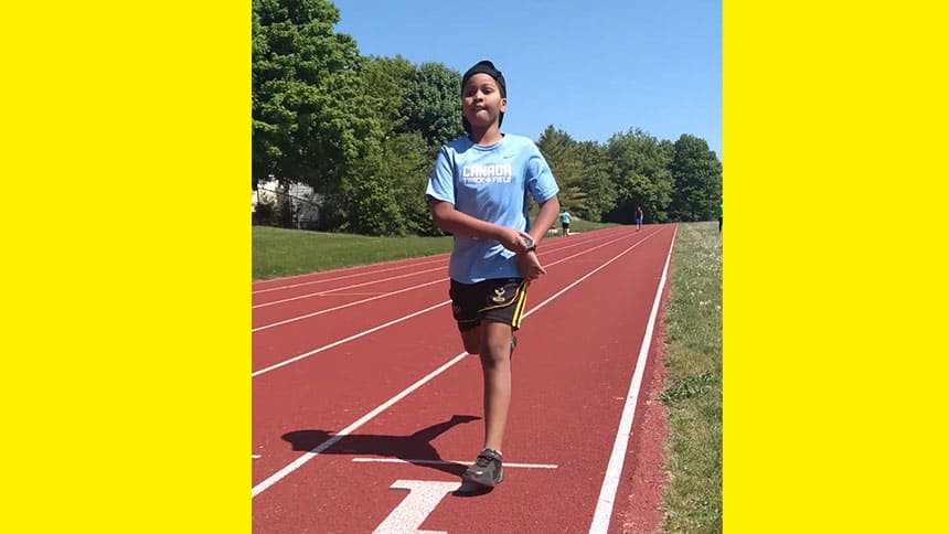 Kid runs on track.