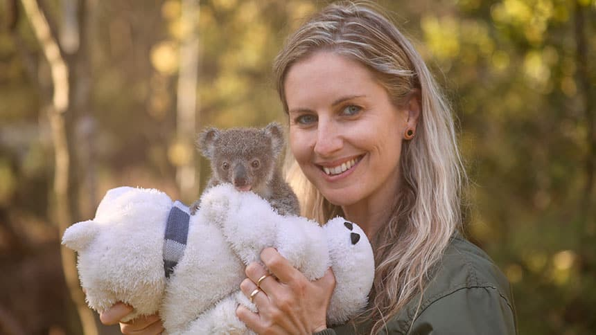 Zoo keeper holds fluffy toy with baby koala perched on top.