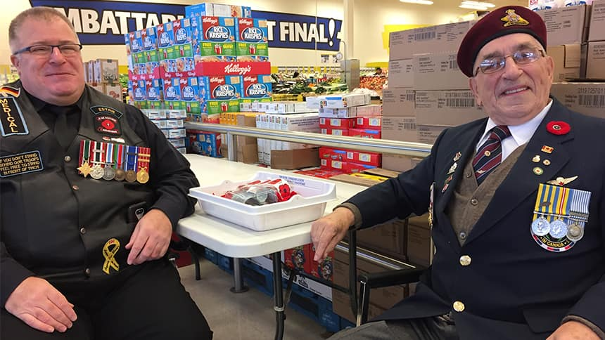 Two veterans sit at a table selling poppies