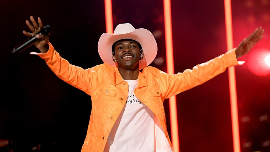 Lil Nas X throws his hands in the air with a big smile.