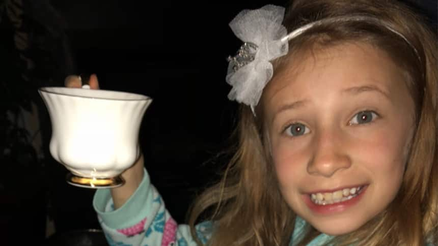 Kaelin Woods holds a tea cup and wears a fascinator in her hair.