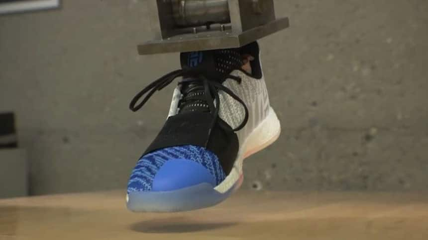 Shoe suspended on what looks like a metal leg.