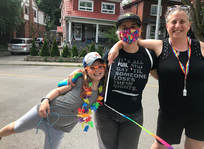 Maayan wearing a mask stands with her two moms.