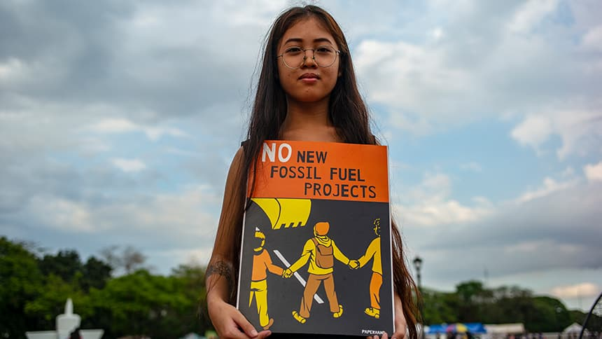 Girl holds poster that says No new fossil fuel projects.